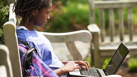 Female student sitting outside working on laptop